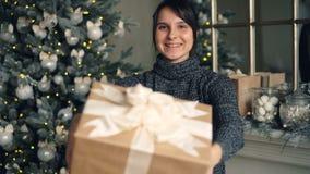 然后伸她的手的微笑的女孩藏品礼物盒画象提供当前祝贺在圣诞节 影视素材
