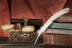 仍然生活葡萄酒 在老胸口和葡萄酒书的被密封的纸卷附近用羽毛装饰在红色背景 库存图片