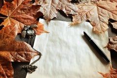 仍然秋天生活 与时钟和墨水笔的老被染黄的纸在秋天槭树附近离开 免版税库存照片