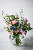 仍然1寿命 一张木古色古香的桌,有混杂的花束的玻璃花瓶 美丽的花 免版税库存图片