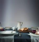 仍然1寿命 水罐,小圆面包,葱,在一张蓝色桌布的大蒜 免版税库存图片