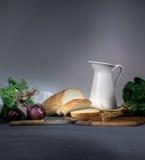 仍然1寿命 水罐,面包,葱,大蒜,在一张蓝色桌布的菠菜 文本的空间 库存图片