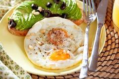 煎的鸡蛋 关闭煎蛋的看法在煎锅的 盐味和加香料的荷包蛋用在生铁平底锅和黑色的荷兰芹 免版税库存照片