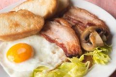 煎蛋、烟肉多士和蘑菇早餐 免版税库存照片