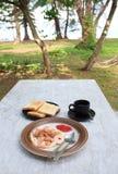 煎蛋、草莓酱面包多士和黑色咖啡在白色木桌上的 库存图片