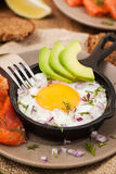 煎蛋、鲕梨和熏制鲑鱼在煎锅 免版税库存照片