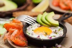 煎蛋、鲕梨和熏制鲑鱼在煎锅 库存图片