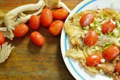 煎蛋充塞了在板材的印地安蘑菇顶部切片西红柿 库存图片