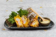 煎蛋卷套可儿螃蟹棍子服务与莴苣和山葵在灰色石板材的色拉调味品在washi日文报纸 免版税图库摄影