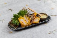 煎蛋卷套可儿螃蟹棍子服务与莴苣和山葵在灰色石板材的色拉调味品在washi日文报纸 免版税库存图片