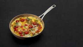 煎蛋卷用蕃茄和草本在黑背景 免版税库存图片