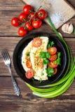 煎蛋卷用西红柿和新鲜的绿色荷兰芹在一个黑铁平底锅 免版税库存图片