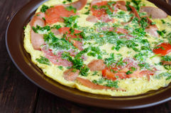 煎蛋卷用香肠和新鲜的蕃茄和草本在黏土板材 库存图片