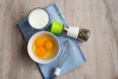 煎蛋卷的,饮食早餐静物画产品在杯子、一杯牛奶,一套混杂的香料和在一蓝色napk的一台搅拌器怂恿 免版税库存图片
