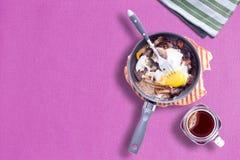煎蛋卷的晴朗的边在紫罗兰色颜色表布料用泥工热的茶 库存照片