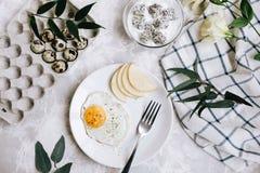 煎蛋和梨早餐在一块白色板材有叉子的 在一个玻璃碗,酸奶和龙在鹌鹑旁边盘子结果实, 库存照片