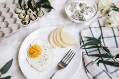 煎蛋和梨早餐在一块白色板材有叉子的 在一个玻璃碗,酸奶和龙在鹌鹑旁边盘子结果实, 库存图片