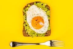 煎蛋晴朗的边在被击碎的鲕梨和黑麦面包开放Fa 免版税库存图片