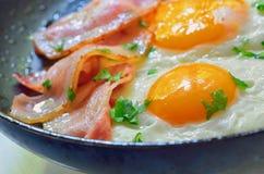 煎蛋用在煎锅的烟肉 免版税库存照片