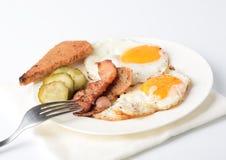 煎蛋用烟肉、腌汁在板材,多士和一把叉子在白色背景 免版税图库摄影