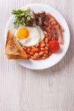 煎蛋用烟肉、豆和多士顶视图垂直 免版税图库摄影