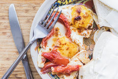 煎蛋用蕃茄、三明治、叉子和刀子 免版税库存图片