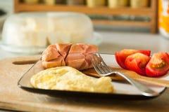 煎蛋用香肠和蕃茄在木桌上 图库摄影