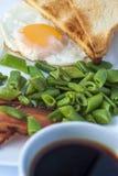 煎蛋,烟肉,青豆, toastsand白色咖啡在轻的背景的 早餐英语 图库摄影