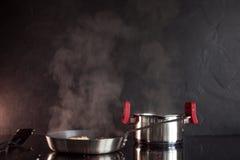煎锅和烹调罐在归纳滚刀,蒸汽上升 黑织地不很细厨房 免版税图库摄影
