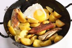 煎锅用土豆和香肠 免版税库存图片