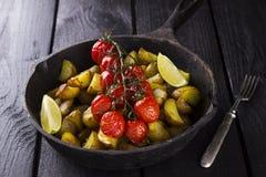 煎锅用油煎的土豆和被烘烤的西红柿在增殖比 图库摄影