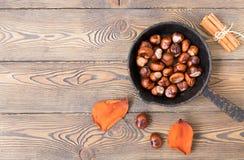 煎锅用烤栗子和五颜六色的秋叶在老木桌上 安置文本 免版税库存图片