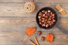 煎锅用烤栗子和五颜六色的秋叶在老木桌上 安置文本 免版税库存照片