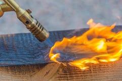 从煤气喷燃器的火是被对待的木材 库存照片