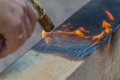 从煤气喷燃器的火是被对待的硬木木材 免版税库存照片