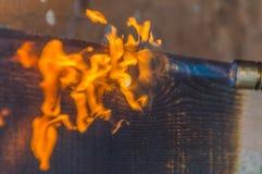 从煤气喷燃器的火被处理烧焦了木头 免版税库存图片