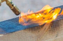 从煤气喷燃器被烧焦的木材的火被处理 免版税库存照片