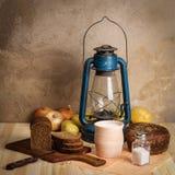 煤油提灯、切板、泥罐用牛奶,黑麦面包、盐和盐盐、葱和土豆在一张木桌上 免版税图库摄影