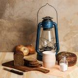 煤油提灯、切板、泥罐用牛奶,黑麦面包、盐和盐盐和葱在一张木桌上 图库摄影