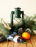 煤油提灯、锥体、冷杉木分支和蜜桔 图库摄影