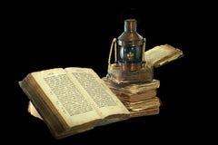 煤油灯和旧书。 免版税库存图片