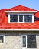 煤渣砌块议院  有塑料窗口和波纹状的板料一个红色屋顶的议院  免版税库存照片