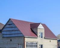 煤渣砌块议院  有波纹状的板料塑料窗口和屋顶的议院  金属外形波浪形状屋顶在房子w的 库存图片