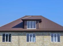 煤渣砌块议院  有波纹状的板料塑料窗口和屋顶的议院  金属外形波浪形状屋顶在房子w的 免版税库存照片