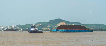 煤炭拖轮拉扯重的被装载的驳船  免版税库存照片