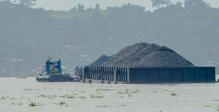 煤炭拖轮拉扯重的被装载的驳船  库存照片