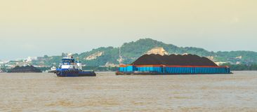 煤炭拖轮拉扯重的被装载的驳船  库存图片