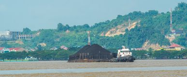 煤炭拖轮拉扯重的被装载的驳船  免版税库存图片