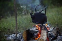 煤烟灰茶壶煮沸和放出在篝火 免版税库存照片