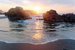 照亮多岩石的海滩的朝阳的金黄光在Wai ` ao,宜兰 库存照片